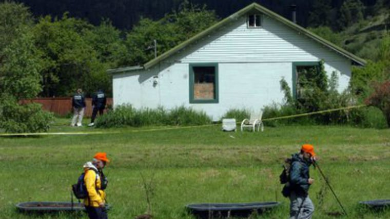 A tracker works in the front yard Tuesday, May 17, 2005, while investigators work around the house where three bodies were discovered Monday, May 16, 2005, near Wolf Lodge Bay east of Coeur d'Alene. (PHOTO: Spokesman Review)