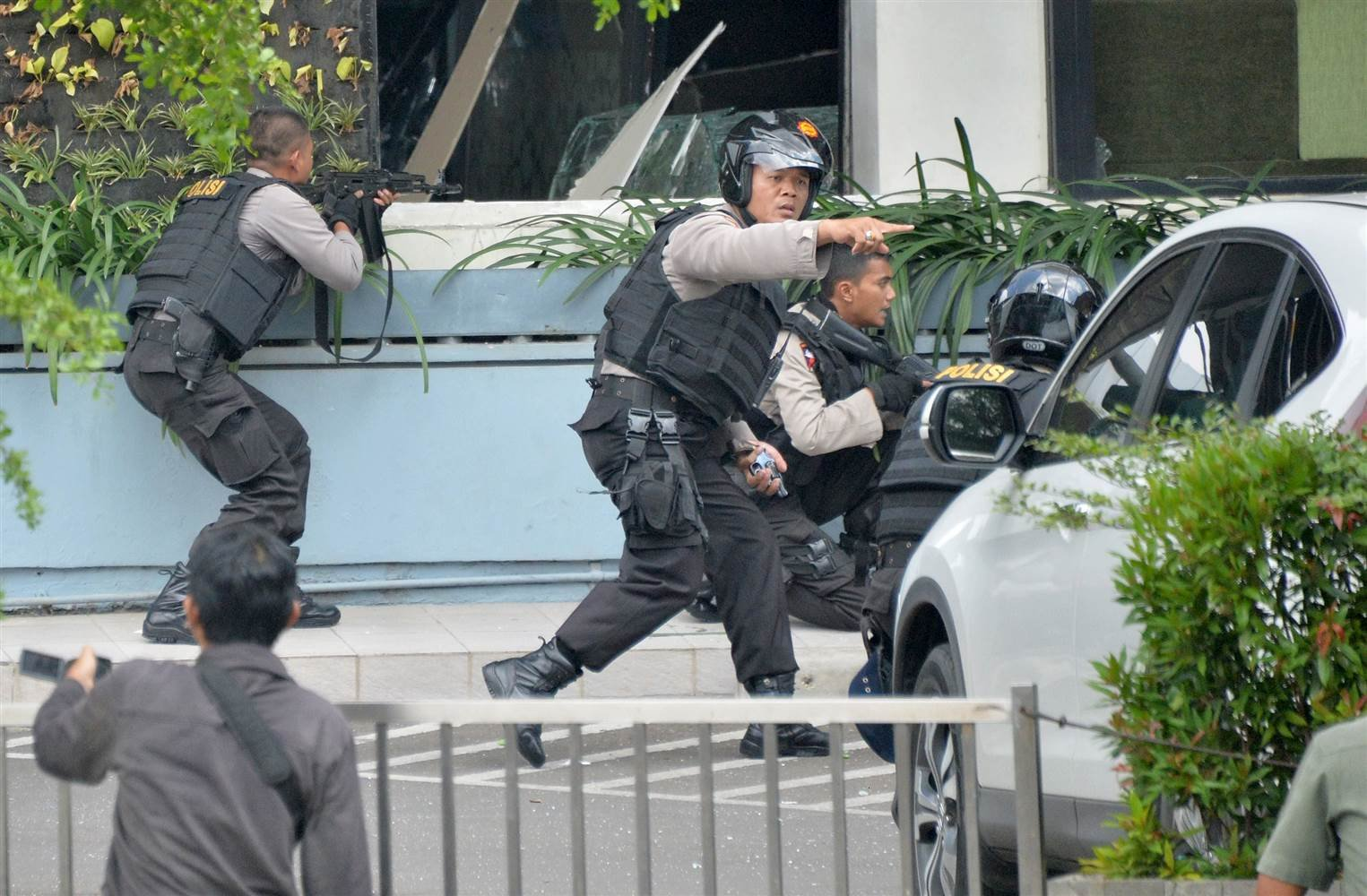 Indonesian police take position and aim their weapons as they pursue suspects outside a cafe after a series of blasts hit the capital, Jakarta, on Thursday. (Bay Ismoyo / AFP - Getty Images)